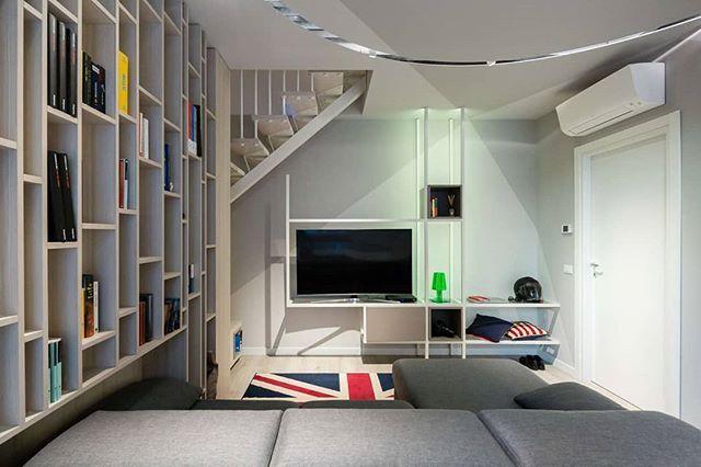 Soggiorno con libreria con ripiani sfalzati e parete attrezzata in