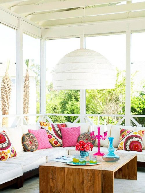 12 White Rooms with Pops of Color: Who knew Better Homes & Gardens was worthy of a gander for modern inspiration? This porch is perfection, with comfy white seating, a contemporary wood table, suzani pillows, and a perfect pink candelabra with a distinctly Danish flair.