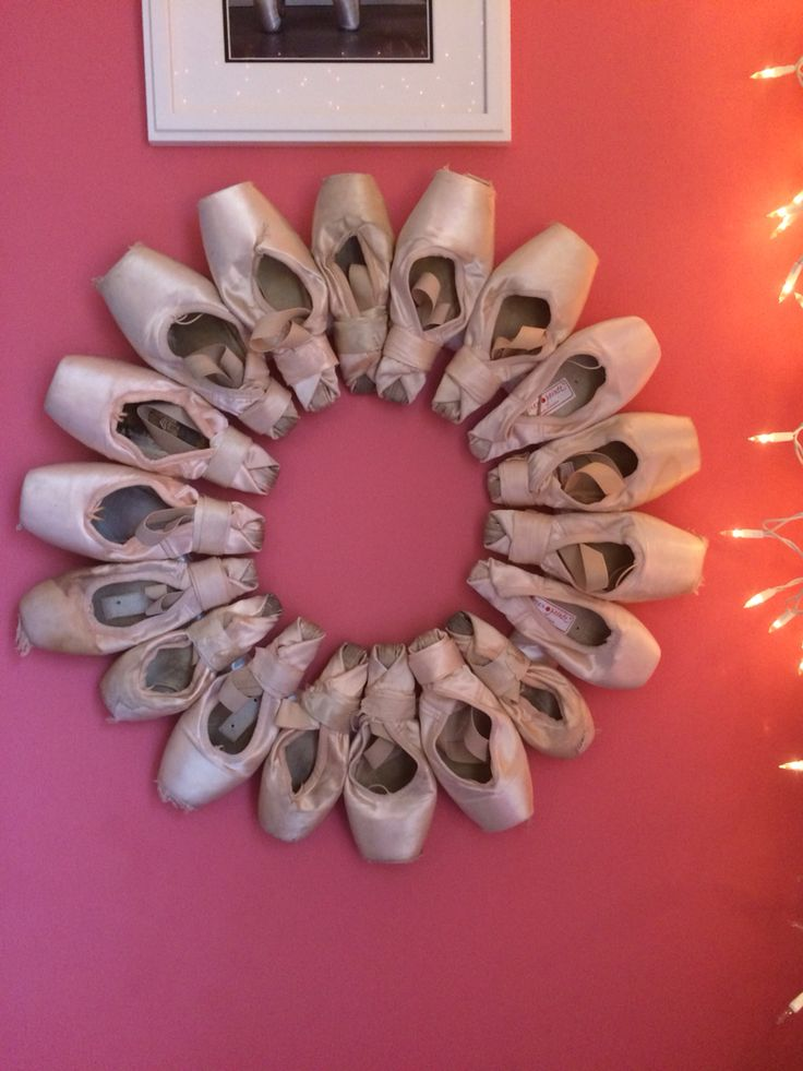 pointe shoe wreath for displaying old pointe shoes. use a metal wire wreath, cover it with ribbon and use E6000 glue for your pointe shoes!