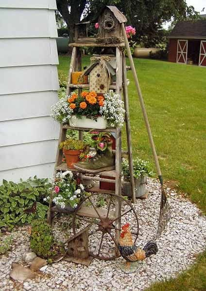 Lovely way to create a shabby vintage look using an old ladder, wheel and plants.