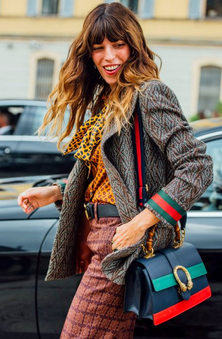 Lou Doillon at Milan Fashion Week wearing Gucci handbag. Street style shot by Tommy Ton.