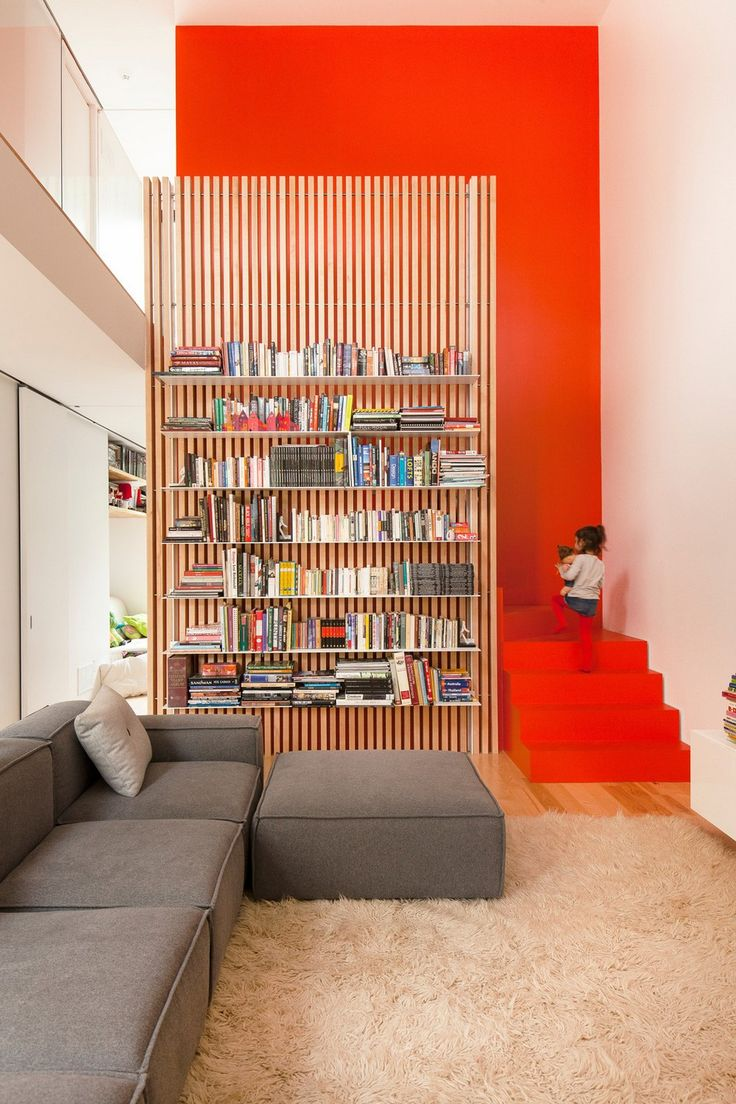 This home features a modern library complete w/ a wood slat bookshelf next to a bright orange stairway. Neutral seating & flooring focus all attention on this home library.