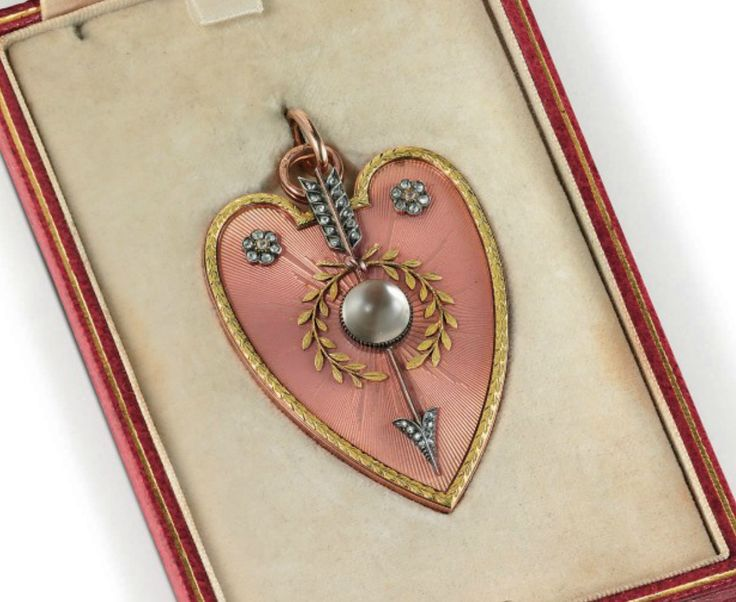 A pendant By Fabergé, with the workmaster's mark of Henrik Wigström, St. Petersburg, 1896-1908, scratched inventory number 9578 Heart-shaped, enameled in translucent salmon-pink over a sunburst guilloché ground, centering a moonstone encircled by a laurel wreath and pierced by a diamond-set arrow, beneath two diamond-set flowerheads, all within a leaf-chased border, with suspension loop, in a fitted red leather