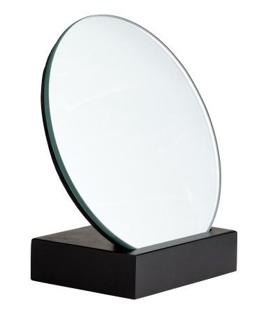 Black. Small, round mirror with a wooden back and base. Diameter of mirror approx. 4 3/4 in., height 4 3/4 in.