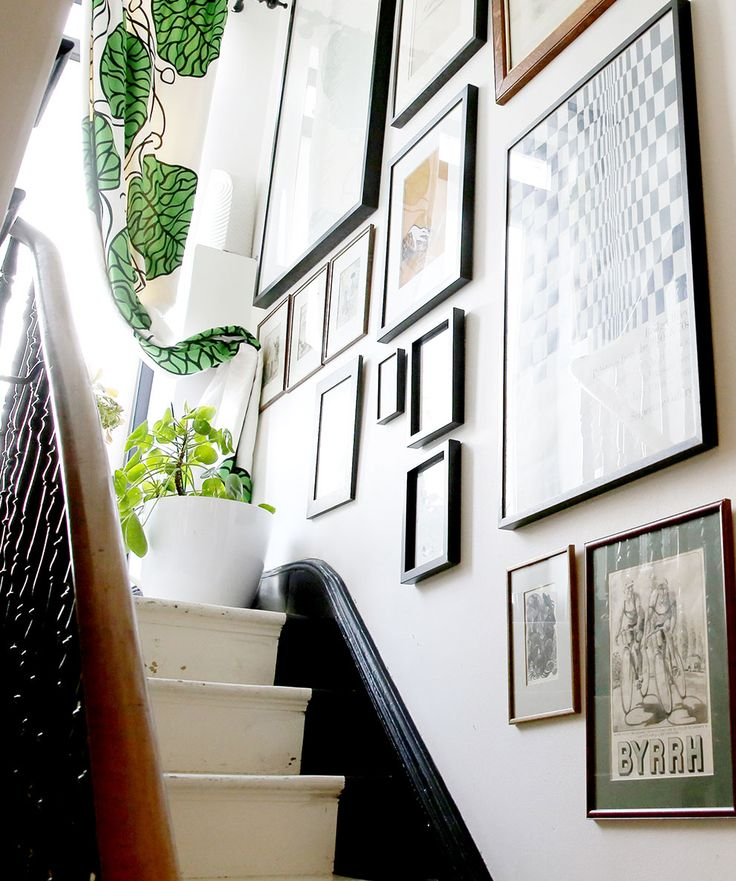 A range of framed images feature on the wall by the stair case.