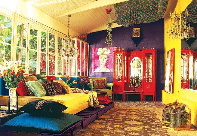 Tapetes megaestampados com florais e motivos orientais recobrem o chão do espaço de estar. Colchão revestido com jacquard amarelo adamascado. As paredes foram pintadas nas cores ameixa e azul-pavão