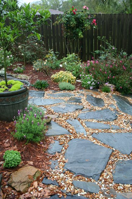 Stones and pea gravel beside the patio, between the rose bushes, with a few potted plants, a bird bath, and maybe a chair or two.