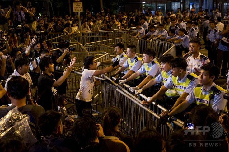 香港(Hong Kong)で、政府庁舎を包囲して梁振英(Leung Chun-ying)行政長官を待つ民主派デモ参加者らに対峙(たいじ)する警官隊(2014年10月2日撮影)。(c)AFP/XAUME OLLEROS ▼2Oct2014AFP|香港の民主派デモ、行政長官官邸を3000人が包囲 http://www.afpbb.com/articles/-/3027783