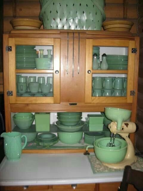 Beautiful collection of antique jadeite displayed in Early American hutch.