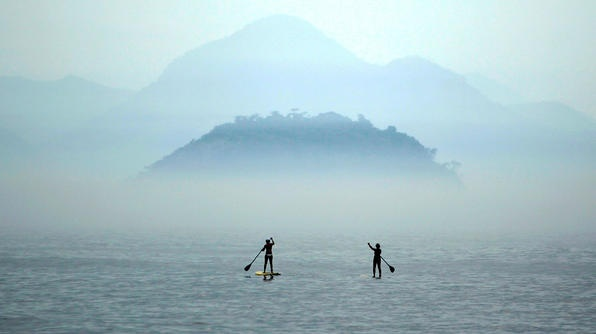 Two women paddle on stand-up paddle boards at Copacabana beach in Rio de Janeiro.