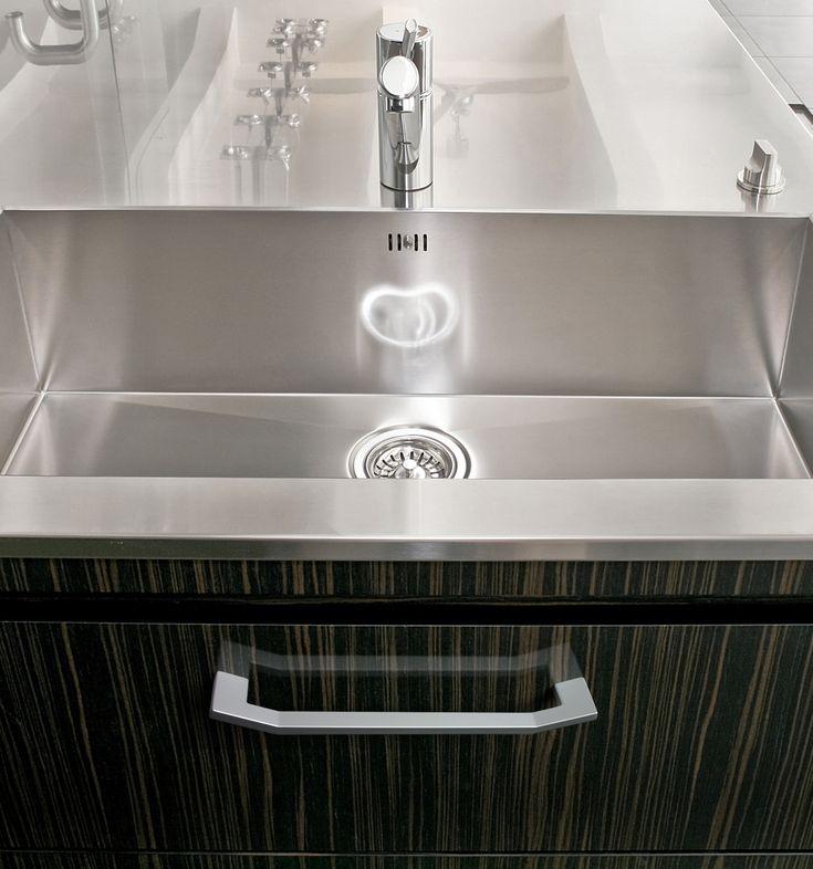 Se trata de un tirador en Cromo Mate modelo Angle sobre un mueble en color marrón oscuro veteado de una cocina o baño.