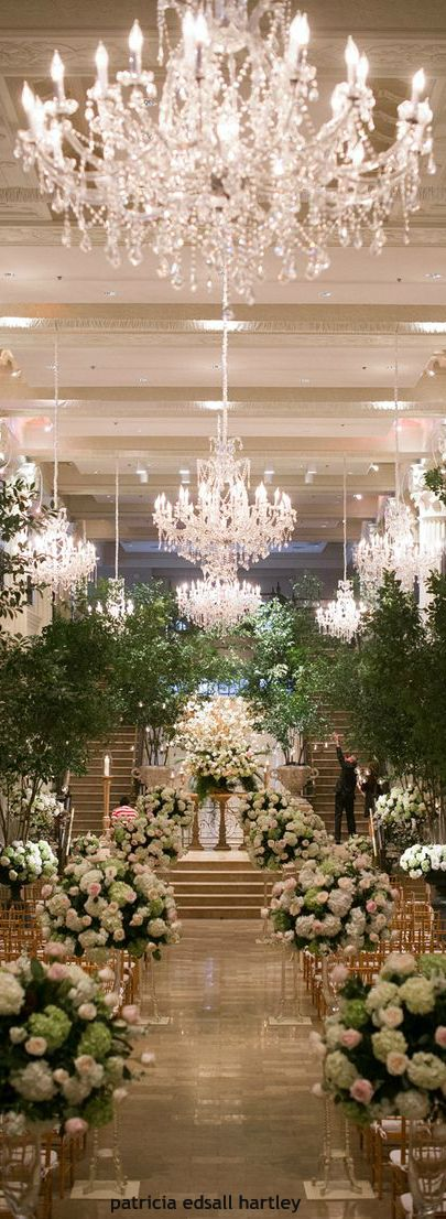 Stunning Ceremony Decor. Love the trees and chandeliers!