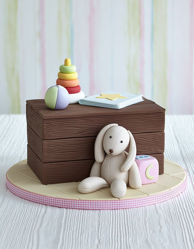 "Zoe Clark: This traditional toy chest cake, complete with a realistic woodgrain effect and cute collection of toys is a simple yet delightful design idea for first birthday celebration or Christening. Here is what you need! Materials: 20 x 12.5cm (8 x 5in), 10cm (4in) deep rectangular cake (See recipes) on a base board (5mm (½"") foam board or cake … Read more..."
