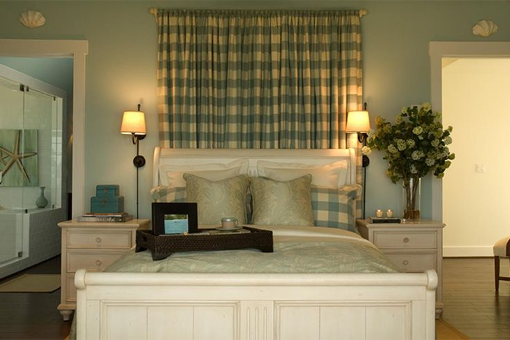 This coastal master bedroom in the 2008 HGTV Dream Home creates a calm feeling with simple furnishings and a creamy color palette that mimics the ocean waves. A panel of checkered drapery shows off the antique sleigh bed and accentuates the room's high ceiling.