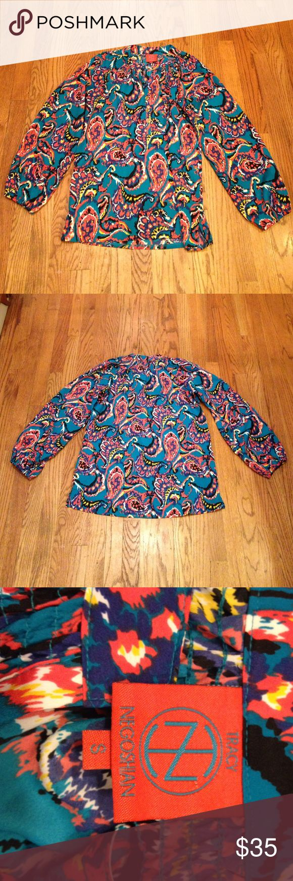 """Tracy Negoshian Tunic Teal Tunic w/ colorful (orange, yellow,blue, white& black) graphic paisley design. Long sleeves & elastic at wrist.  V-neck w/ stand up collar &  smocking at neckline. 3 gold colored buttons on front. Measures 28"""" from top to bottom. Sleeves measures 25"""" shoulder to wrist. NWOT Tracy Negoshian Tops Tunics"""