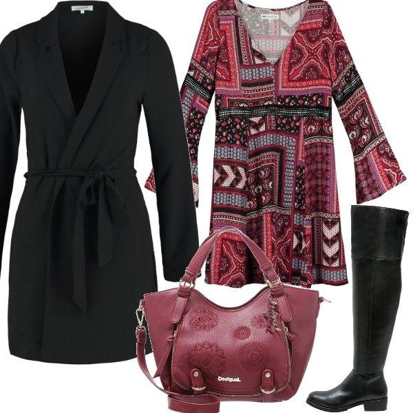 Una fantasia che gioca con il rosso e il nero nel vestito corto con scollo a v, indossato con un paio di stivali alti neri e un cappotto con cintura da annodare in vita. E' rossa, invece, la borsa con decorazioni tono su tono.