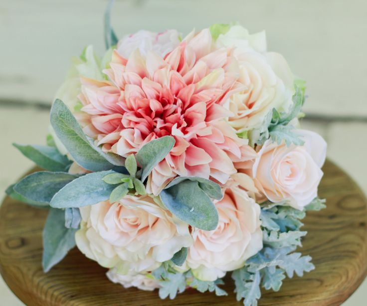 With a soft and feminine color scheme, this bouquet can be a hit during any wedding season. Featured is the Medium/Regular size Bouquet. Includes: - Pink Blush Large Dahlia - Blush Roses - Lambs Ear S