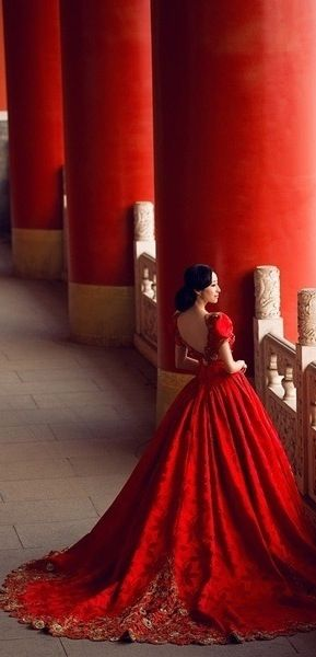 Seeing red. A magnificent ruby red dress set against grand red palace pillars.