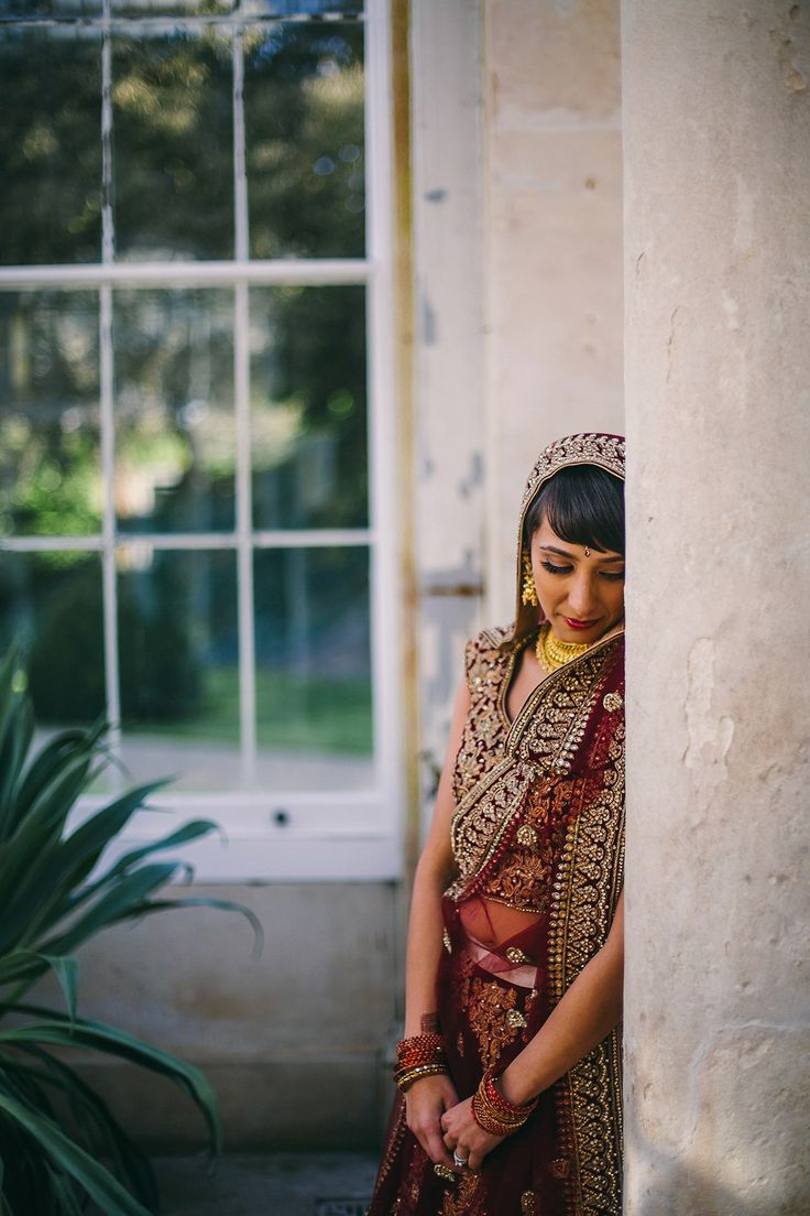 Sabrina wore a red lehenga for her multicultural wedding including an Anglican and Hindu ceremony at Syon Park in London. Photography by Viva La weddings.