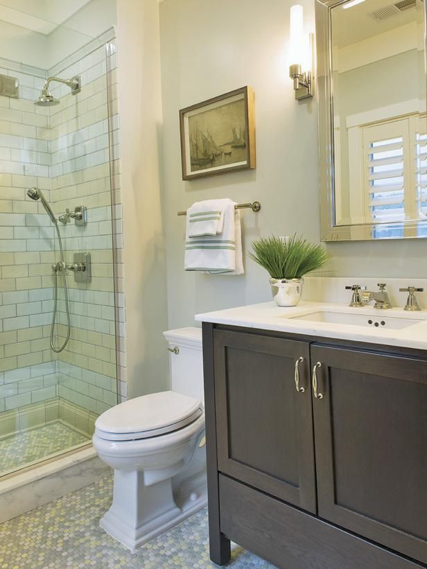 This guest bathroom features a steam shower with rain showerhead penny tile flooring and carrera marble countertops the neutral tiled shower maintains a