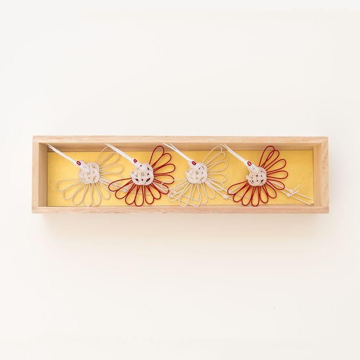 長寿を象徴するおめでたい鳥として知られる鶴と、同じく吉祥文様である菊の花を組み合わせた「菊鶴」の紋を、水引細工で立体化した箸置き…