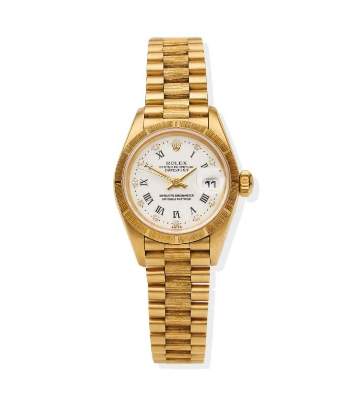 A Lady's gold Datejust wristwatch, Rolex, circa 1996. Automatic. 26mm. Ref: 69278. Serial number T351436. White dial with applied diamond indexes and black printed Roman numerals, tree bark bezel, centre sweep seconds, date aperture at 3 o'clock. Case, dial, and movement signed. Original tree bark president bracelet numbered 9235. Box, papers, swing tag, two extra links. - Price Estimate: $18000 - $22000