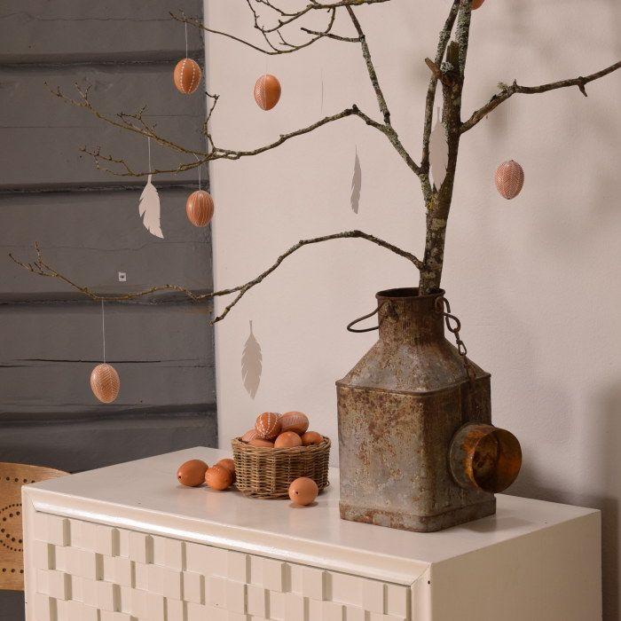 Kvist med hängande vita pappersfjädrar och bruna ägg