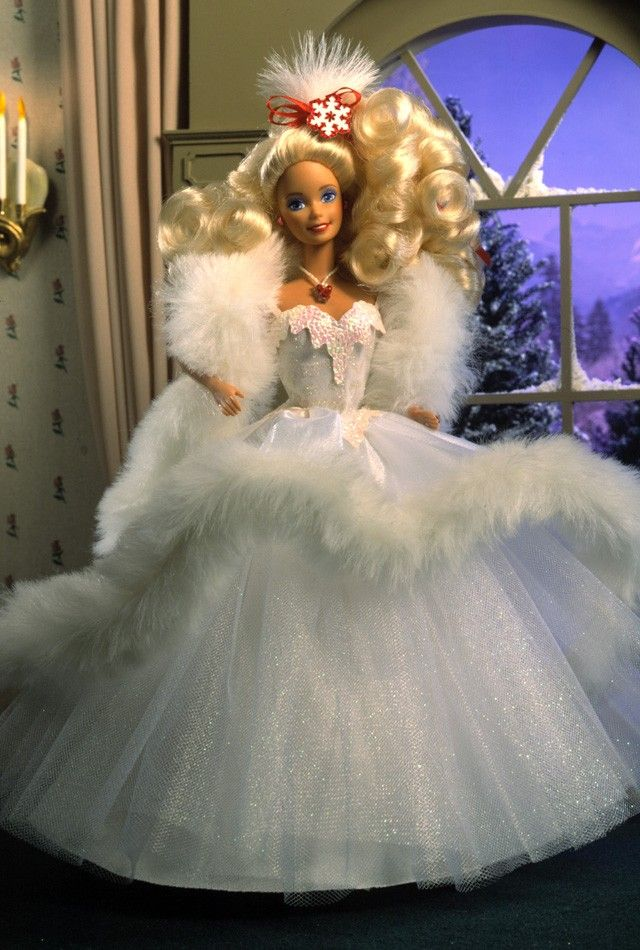 1989 Happy Holidays® Barbie® Doll | Barbie Collector:  Second in the Happy Holiday series, Barbie is a vision of white in this fabulous tulle gown with a faux fur-trimmed overskirt and stole.  Her long blonde hair is curled in ringlets, and accented by a snowflake-decorated hair band that matches the accompanying snowflake ornament.  (Big on my wish list)
