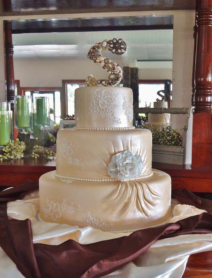 """Soft Gold Pleats and Brushed Embroidery - Soft gold fondant with ivory piping.  Gumpaste flower embellished with rhinestones. Jewel embellished monogram topper.  I designed the cake to match the bride's Maggie Sottero """"Embrace"""" dress."""