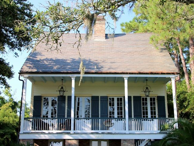 From Trippaluka Style....Raised Creole Cottage listed on the National Register of Historic Places in Old Mandeville, LA, has a Haint Blue porch ceiling, French Quarter Green shutters, and Bevolo gas lanterns