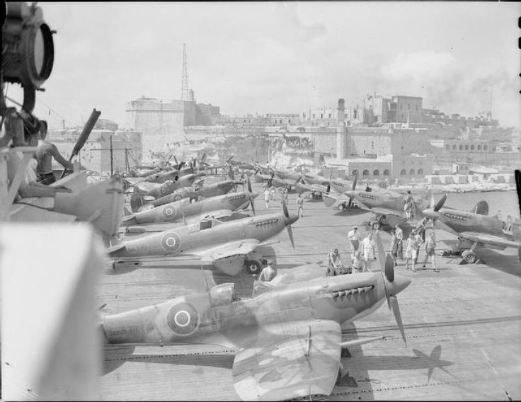 Under the bombed bastions of the entrance to Grand Harbour, Valletta, Malta, an escort carrier arrives with the deck loaded with Supermarine Seafire MkIII (recognisable by their detached wingtips).