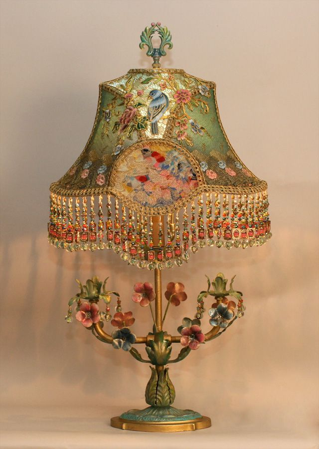 Ornate, hand-painted dimensional 1920s tole lamp with flowers, leaves and drops holds a hand-dyed Flora and Fauna silk lampshade. The shade is ombre-dyed from pale robins egg blue into slightly darker hue at the bottom. The shade is covered with a colored floral embroidered net and then overlaid with a colorful array of metallic couched asian appliques. The center ovals are lush metallic lame. The shade has glass and hand beaded fringe in matching tones and the base has coordinating drops…