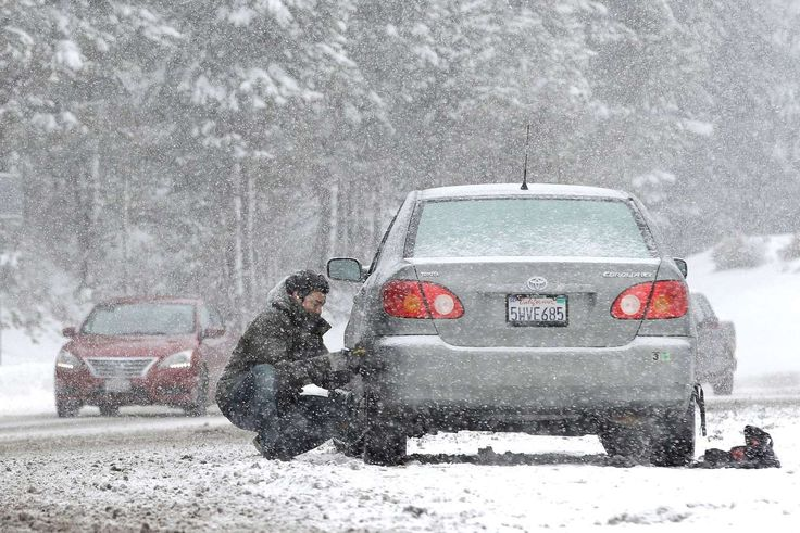 A motorist puts on snow chains near Echo Summit, Calif., Tuesday, Jan. 3, 2017. The California Department of Water Resources held the first manual snow survey of the season near Phillips Station near Echo Summit on Tuesday. The survey showed the snowpack at 53 percent of normal at the site for this time of year.