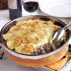 Jachtschotel recept NGREDIENTEN 6 PERSONEN  800 g sukadelapjes of magere runderlappen, in dobbelstenen 2 eetlepels bloem 2 eetlepels olie 100 g boter + een beetje om in te vetten 50 g spekblokjes 2 uien, gesnipperd 4 kruidnagels 10 jeneverbessen, gekneusd  2 laurierblaadjes 300 ml rode wijn 2 plakjes ontbijtkoek, in dobbelstenen 900 g aardappelpuree (zelfgemaakte) 2 appels, geschild en in ringen 2 beschuiten, verkruimeld