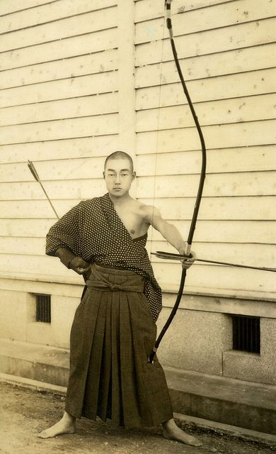 Kyudo - Way of the Bow 1930s  The Yumi (Japanese Bow) is an asymmetrical longbow over two metres in height that is traditionally made of bamboo, wood and leather, while the Ya (arrows) of this period have bamboo shafts with eagle or hawk feather fletchings. Practiced for centuries as both a Gendai budo (Martial Art) and a form of Zen meditation, the sport of Kyudo is still widely studied throughout Japan. S)