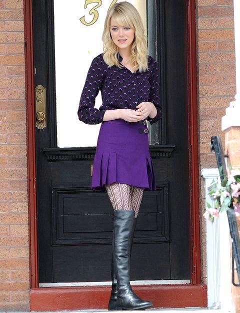 Nos gusta la manera en la queEmma Stone combina sus botas planas en negro con una falda tableada en morado y blusa estampada en este mismo tono.
