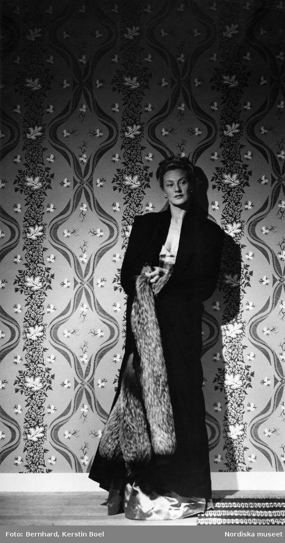 Modell i lång svart kappa, hellång aftonklänning och pälsboa, står framför mönstrad tapet. Fotograf: Kerstin Boel Bernhard, ca 1960-1965