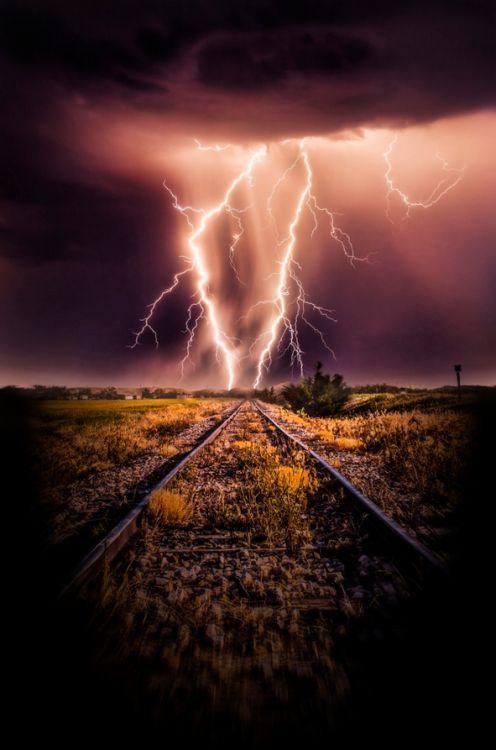 Twin lighting strikes far down the tracks.