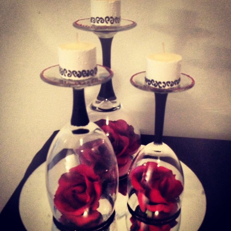 Burgundy flowers inside  wine glasses with candles on top. Good decoration for holidays, weddings, etc.