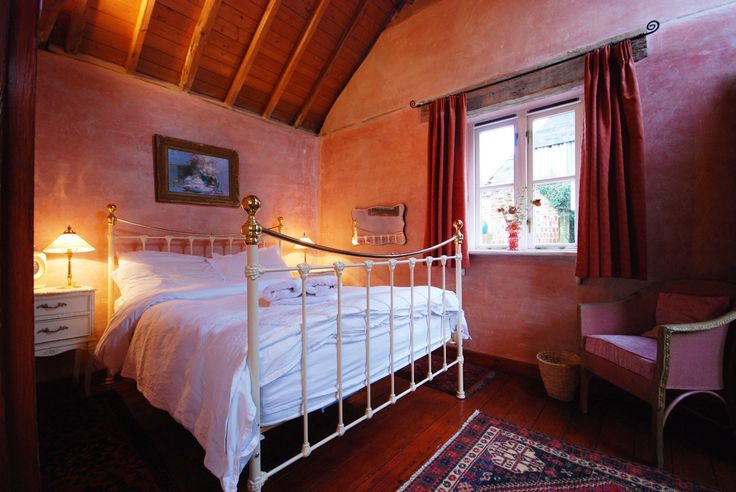 A romantic bedroom with a brass framed bed at Rose Cottage.