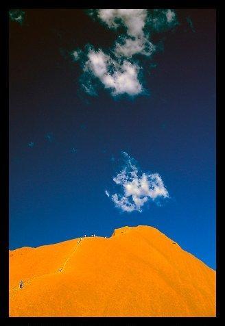 Hikers ascend Ayers Rock. Uluru-Kata Tjuta National Park, Northern Territories, Australia.