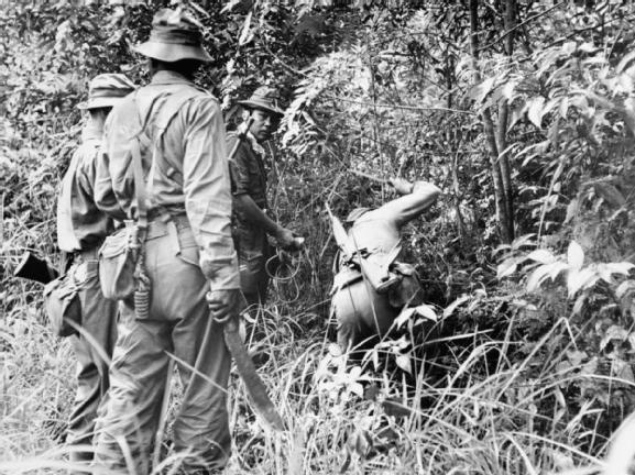 An infantry patrol use their parangs to cut a trail through jungle undergrowth during the Malayan Emergency