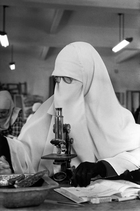 EGYPT. Cairo. 1987. A student wearing the nigab, the full Islamic veil in front of a microscope in the biology department of Cairo University. By Abbas