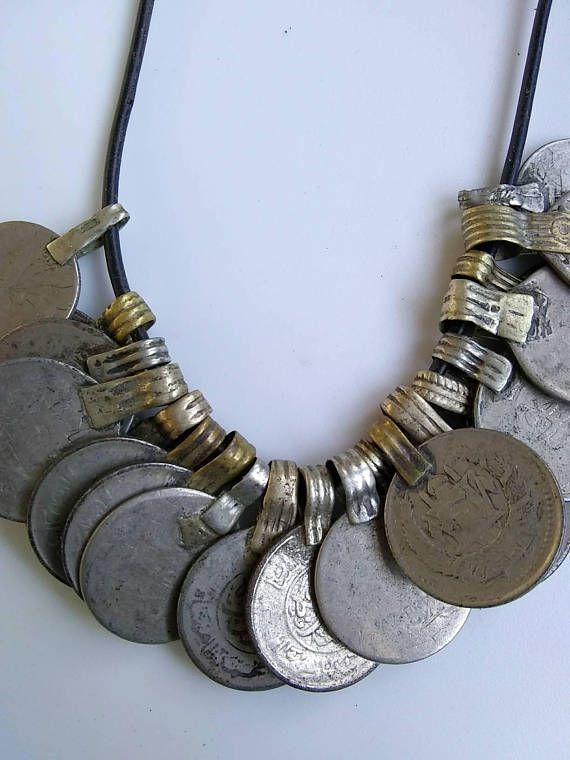 an antique cluster of money-- old arabian coins are featured on this gypsy necklace. perfect for belly dance! the smooth black rubbery cord is unobtrusive. charms are in silver. coins extend from wide, flat rib hammered brass loops and have arabic characters on one side and a spired
