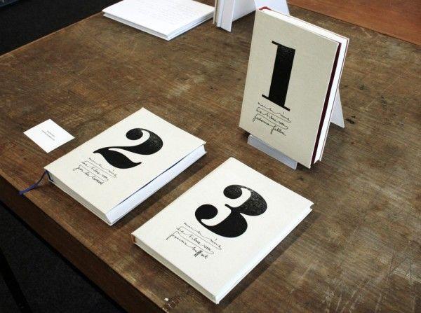 """Der Name meines fiktiven Avantgardefilmverlags lautet """"mise-en-scène """" und beschreibt in der Filmwelt das in Szene setzten. Der Schriftzug ist in Handschrift geschrieben, die Bindestriche werden durch einen längeren Bogen, der die Worte miteinander verbindet, angedeutet. Als Gegensatz zu dem Logo, das in seiner Strichstärke sehr gleichmäßig ist, stehen die Zahlen in der kontrastreichen Bodoni [...]"""