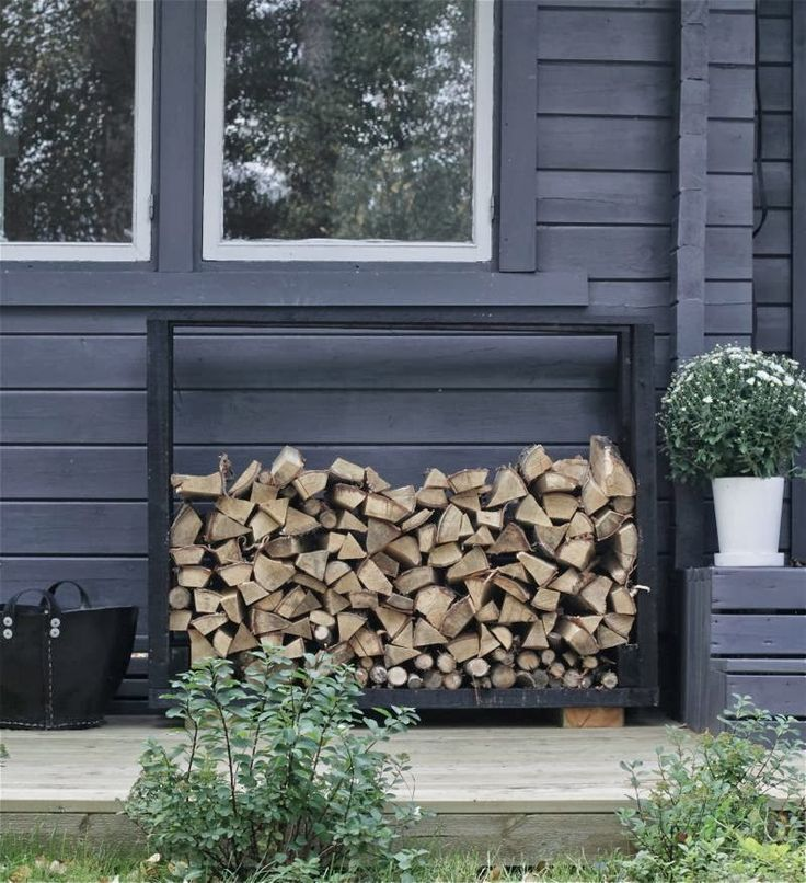 Dark grey or anthracite is a great background color in any garden scheme: never obtrusive, easy to match.   And by the way: Great way to store your firewood.