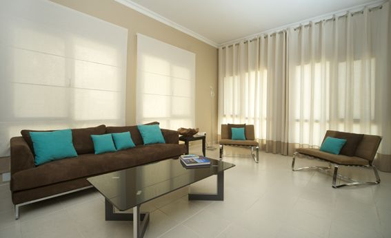 Plain eyelet curtains and blinds to match the modern feel of a bachelor's apartment in Dubai