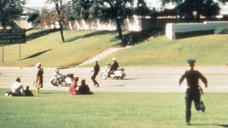 "Babushka lady is on the left, close to the road and wearing a scarf. The Babushka Lady is a nickname for an unknown woman present during the 1963 assassination of President John F. Kennedy who might have photographed the events that occurred in Dallas' Dealey Plaza at the time President John F. Kennedy was shot. Her nickname arose from the headscarf she wore similar to scarves worn by elderly Russian women (бабушка – babushka – literally means ""grandmother"" or ""old woman"" in Russian)."
