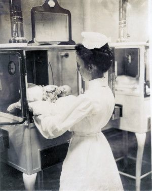 Nurse with an infant in the Baby Incubator exhibit on the Pike at the 1904 World's Fair. Jessie Tarbox Beals.