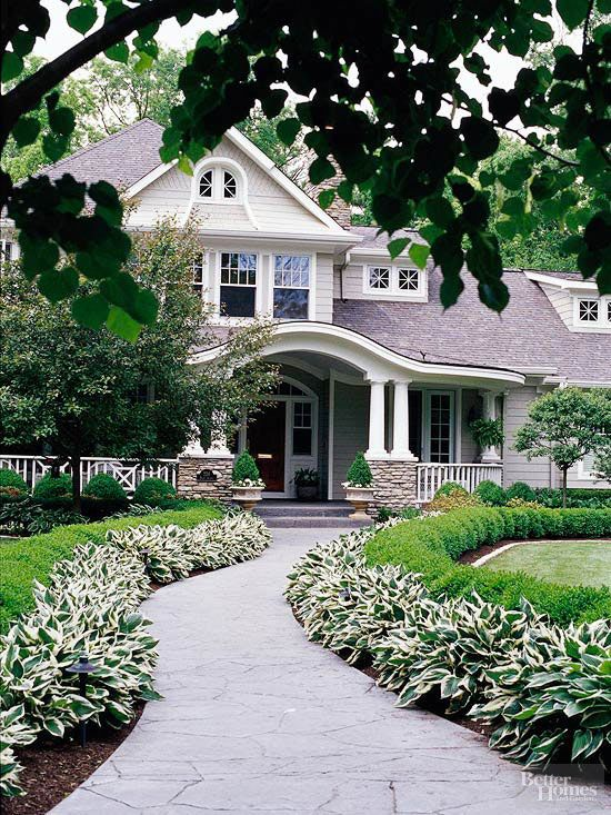 Transform your front walk into a stylish statement by edging it in easy-care plants such as variegated hosta and boxwood.